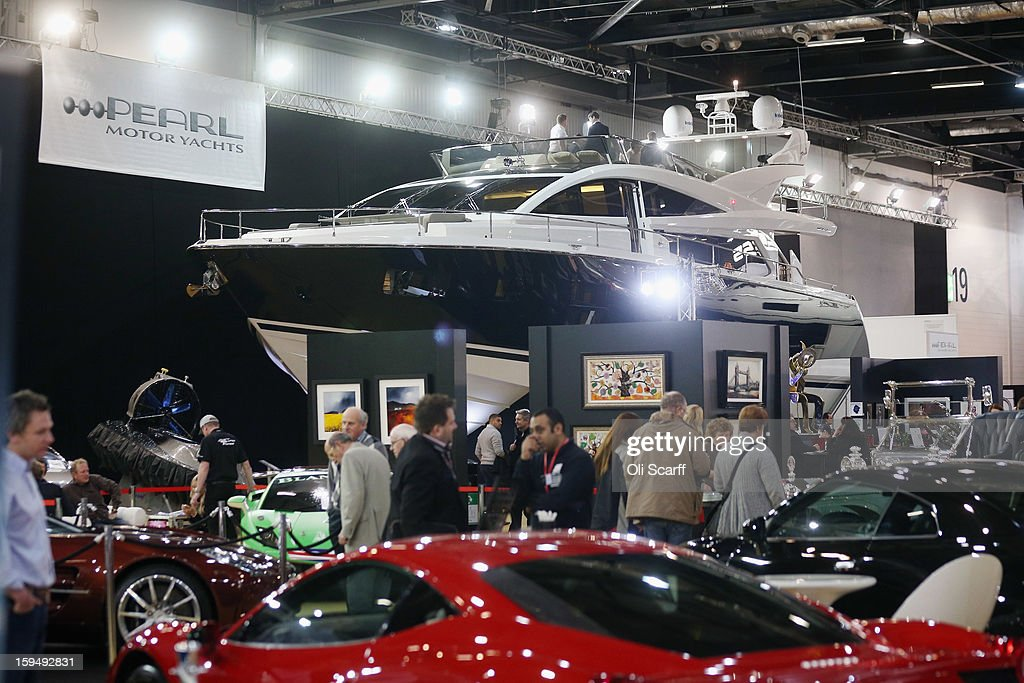 Visitors admire the boats and cars on display at the 2013 London Boat Show, held at the ExCeL Centre, on January 14, 2013 in London, England. Until January 20, 2013 the London Boat Show will showcase, demonstrate and sell maritime equipment ranging from luxury yachts to dinghies.