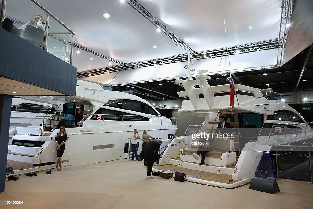 Visitors admire the boats on display on the Fairline stand at the 2013 London Boat Show, held at the ExCeL Centre, on January 14, 2013 in London, England. Until January 20, 2013 the London Boat Show will showcase, demonstrate and sell maritime equipment ranging from luxury yachts to dinghies.