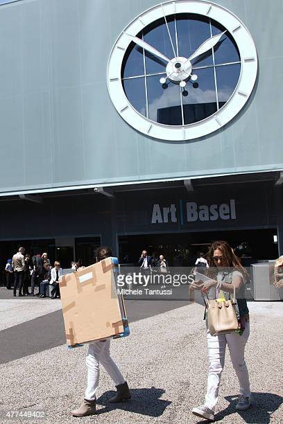 Visitors and buyers exit the exposition hall carrying a newly purchased Paint during the opening day at Art Basel on June 17 2015 in Basel...