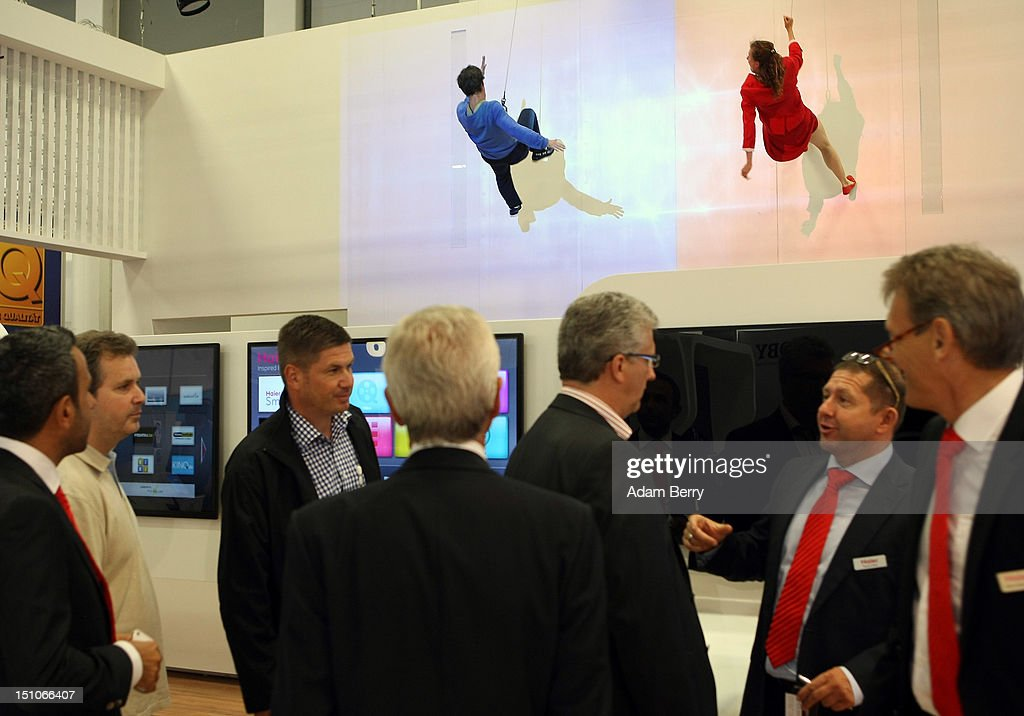 Visitors and employees talk to one another as performers dance on a wall at the Haier stand during the Internationale Funkausstellung (IFA) 2012 consumer electronics trade fair on August 31, 2012 in Berlin, Germany. Microsoft, Samsung, Sony, Panasonic and Philips are amongst many of the brands showcasing their latest consumer electronics hardware, software and gadgets to members of the public from August 31 to September 5.