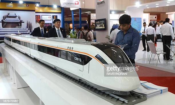 Visitors and exhibitors look at CRH train models on the stand of China Northern Locomotive and Rolling Stock Industry Corporation during the...