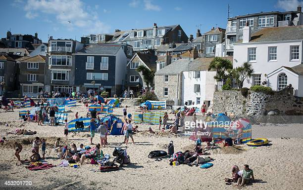 Visitors and holidaymakers enjoy the fine weather as they gather on the Harbour Beach on August 4 2014 in St Ives Cornwall England A recent survey by...