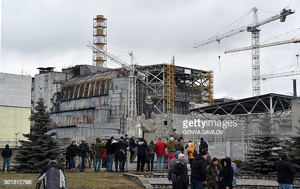 Visitors and journalists gather in front of a shelter and containment area built over the destroyed fourth block of Chernobyl's old nuclear power...