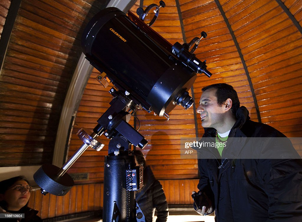 Visitors and members of Naples amateur astronomy association 'Unione Astrofili Napoletani' stand by a telescope during observations to refute the theories of the Mayan 'prophecy' of the world's destruction, late on December 20, 2012 at the astronomical observatory of Capodimonte in Naples. The December 21 mystery stems from a carved stone found in Tortuguero, a Mayan site in Mexico.