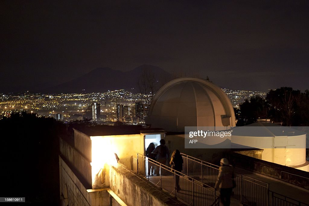 Visitors and members of Naples amateur astronomy association 'Unione Astrofili Napoletani' enter the astronomical observatory of Capodimonte, facing the Vesuvio volcano, for observations to refute the theories of the Mayan 'prophecy' of the world's destruction, late on December 20, 2012 in Naples. The December 21 mystery stems from a carved stone found in Tortuguero, a Mayan site in Mexico. AFP PHOTO / CARLO HERMANN