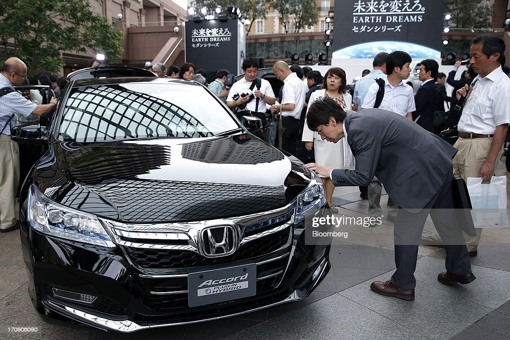 Visitors and members of the media examine a Honda Motor Co. Accord plug-in hybrid sedan displayed at its unveiling in Tokyo, Japan, on Thursday, June 20, 2013. Honda, Japan's third-largest carmaker, unveiled a hybrid sedan at a 20 percent higher price than Toyota Motor Corp.'s gasoline-electric Camry, betting drivers will pay extra for fuel economy. Photographer: Kiyoshi Ota/Bloomberg via Getty Images