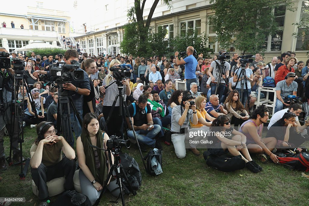 Visitors and reporters attend the conclusion of the latest artist/activist event by the Center for Political Beauty (Zentrum fuer Politische Schoenheit) in the garden of the Gorki theater on June 28, 2016 in Berlin, Germany. The event, called 'Devour Refugees', is meant to bring attention to the plight of refugees seeking to reach Europe. The activsts had contracted a passenger plane to bring 100 Syrian refugees from Turkey to Germany, though the flight was reportedly cancelled today. For the last two weeks the activists have maintained a cage with tigers outside the theater as part of the conceptual piece.