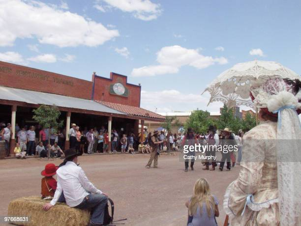 Visitors and tourists seen on the side of the street along with costumed actors watch a reenactment of a western scene in Tombstone Arizona 2005
