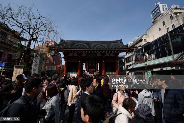 Visitors and tourists stand in front of the Kaminarimon an entrance gate to the Sensoji temple in the Asakusa district of Tokyo Japan on Monday March...