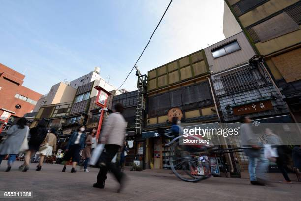 Visitors and tourists walk along a shopping street in the Asakusa district of Tokyo Japan on Monday March 20 2017 Japan's land prices will be...