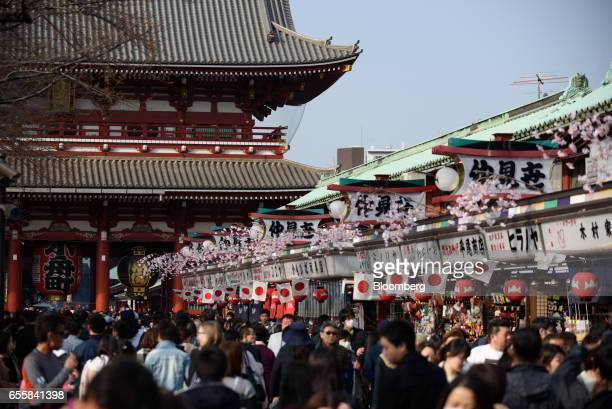 Visitors and tourists walk along a shopping street leading to the Sensoji temple in the Asakusa district of Tokyo Japan on Monday March 20 2017...