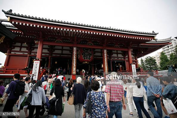 Visitors and tourists walk towards the main hall at the Sensoji temple in Tokyo Japan on Wednesday May 6 2015 Foreign visitors to the nation totaled...