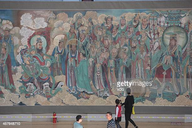 Visitors appreciate the fresco of Yongle Temple at a gymnasium on October 26 2014 in Xiangyang Hubei province of China Painter Liu Yongzhi facsimiled...