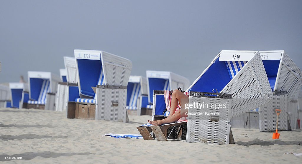 Visitors are pictured lying in a roofed wicker beach chair at the Brandenburger Beach on July 22, 2013 in Westerland, Germany. The weather forecast, for the next three days, predicts sunny weather with heighs of 30 Celsius for the north of Germany.