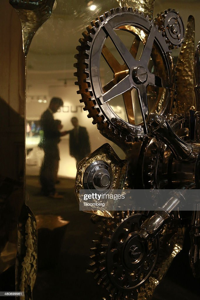 Visitors are reflected above the combination lock of a 'Millionaire' safe, produced by Boca Do Lobo, at the company's booth during the Baselworld luxury watch and jewelry fair in Basel, Switzerland, on Thursday, March 27, 2014. Over 1,400 companies from the watch, jewelry and gem industries will display their latest innovations and products to more than 120,000 visitors at this year's luxury show. Photographer: Gianluca Colla/Bloomberg via Getty Images