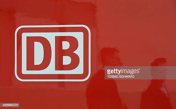 Visitors are reflected as they pass by a logo of German railway operator Deutsche Bahn during the opening day of the Innotrans International Trade...