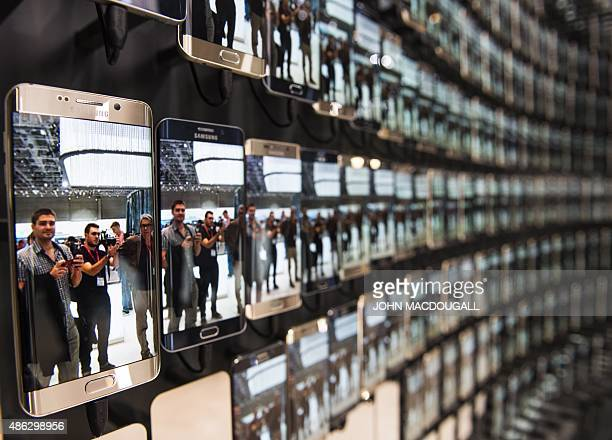 Visitors are reflected in numerous Samsung Galaxy S6 edge smartphones at the booth of South Korean electronics giant Samsung ahead of the opening of...