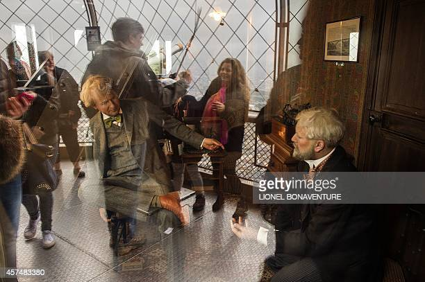 Visitors are reflected on May 10 2014 in the window of a display showing Gustave Eiffel on the third floor of the Eiffel Tower in Paris AFP PHOTO /...