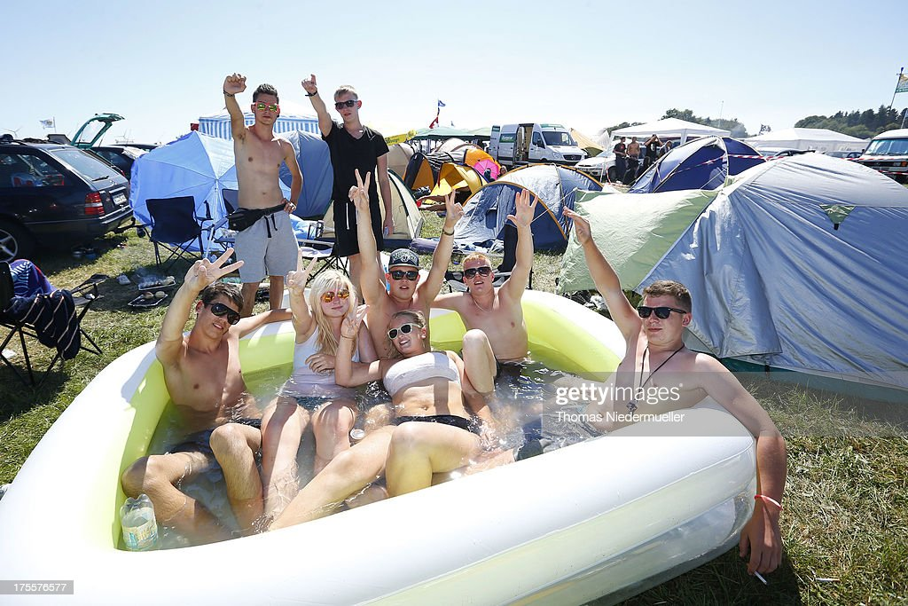 Visitors are seen at the camping village of the 'Nature One' massive rave, held at the former US rocket base Pydna on August 3, 2013 in Kastellaun, Germany.