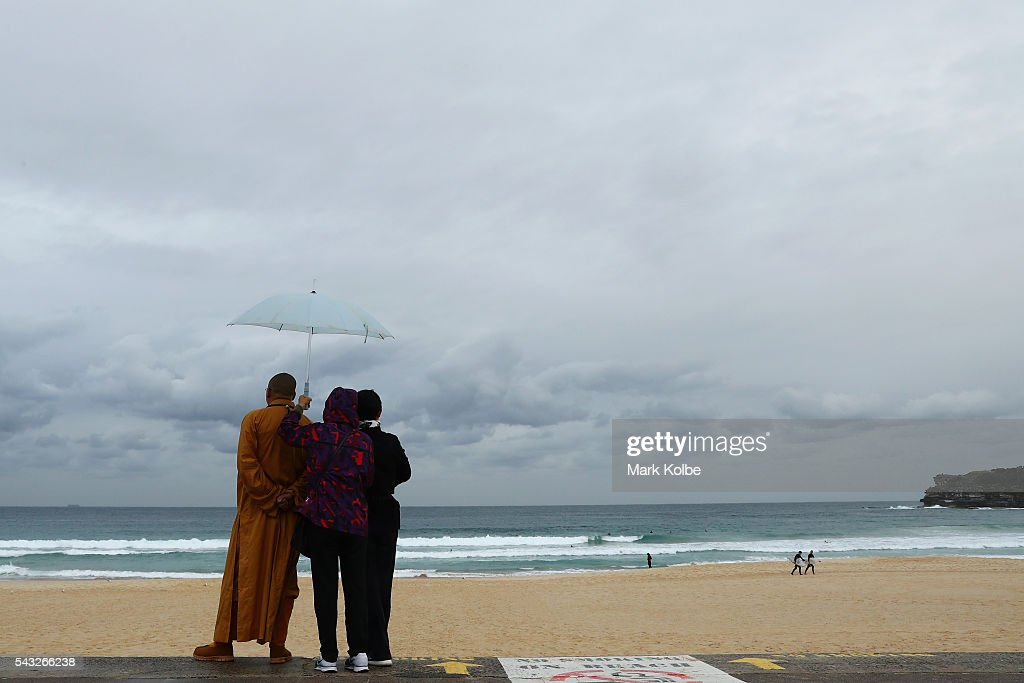 Visitors are seen huddling under an umbrella as they watch surfers catch waves at Bondi Beach on June 27, 2016 in Sydney, Australia. Sydney experienced its coldest day of the year on Sunday, and more icy weather is forecast for later in the week when a second cold front hits later in the week.