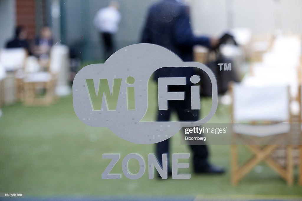 Visitors are seen in a cafe area behind a sign indicating a free WiFi zone at Mobile World Congress in Barcelona, Spain, on Wednesday, Feb. 27, 2013. The Mobile World Congress, where 1,500 exhibitors converge to discuss the future of wireless communication, is a global showcase for the mobile technology industry and runs from Feb. 25 through Feb. 28. Photographer: Simon Dawson/Bloomberg via Getty Images