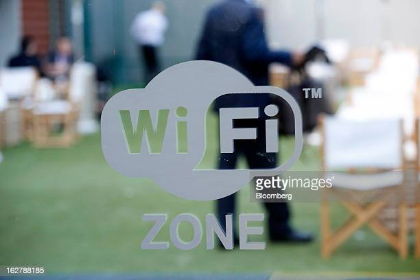 Visitors are seen in a cafe area behind a sign indicating a free WiFi zone at Mobile World Congress in Barcelona Spain on Wednesday Feb 27 2013 The...