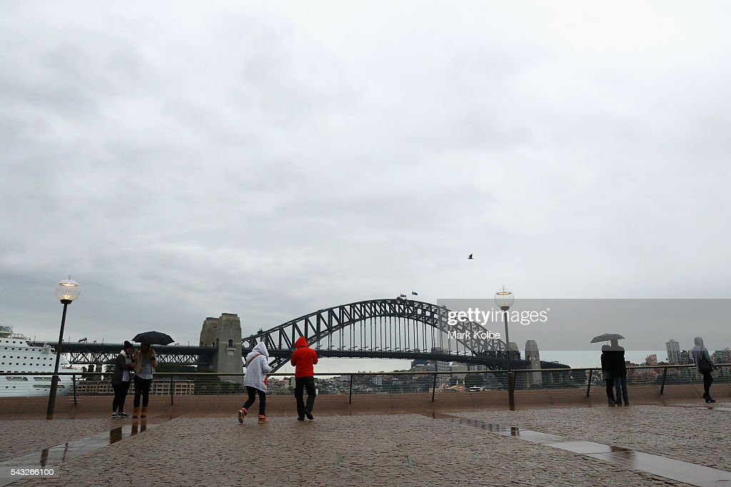 Visitors are seen in winter jackets and huddled under umbrellas as they view the Sydney Harbour Bridge on June 27, 2016 in Sydney, Australia. Sydney experienced its coldest day of the year on Sunday, and more icy weather is forecast for later in the week when a second cold front hits later in the week.