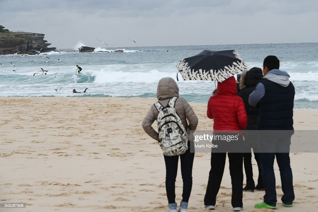 Visitors are seen in winter jackets and huddling under umbrellas as they watch surfers catch waves at Bondi Beach on June 27, 2016 in Sydney, Australia. Sydney experienced its coldest day of the year on Sunday, and more icy weather is forecast for later in the week when a second cold front hits later in the week.