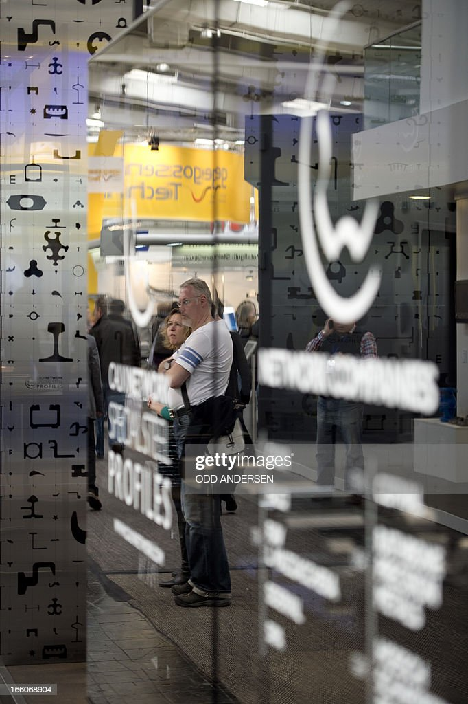 Visitors are seen reflected in the tinted glass of Italian steel company Calvi's booth at the Industrial fair in Hannover in Hanover on April 8, 2013.