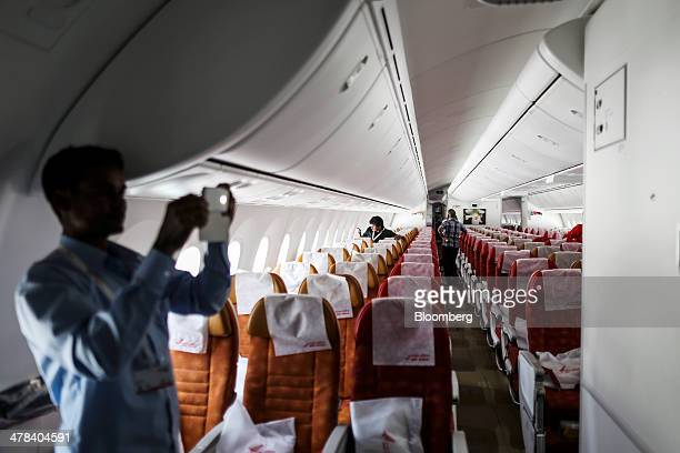 Visitors are seen taking photographs inside a Boeing Co 787 Dreamliner aircraft operated by Air India Ltd on display during the India Aviation 2014...