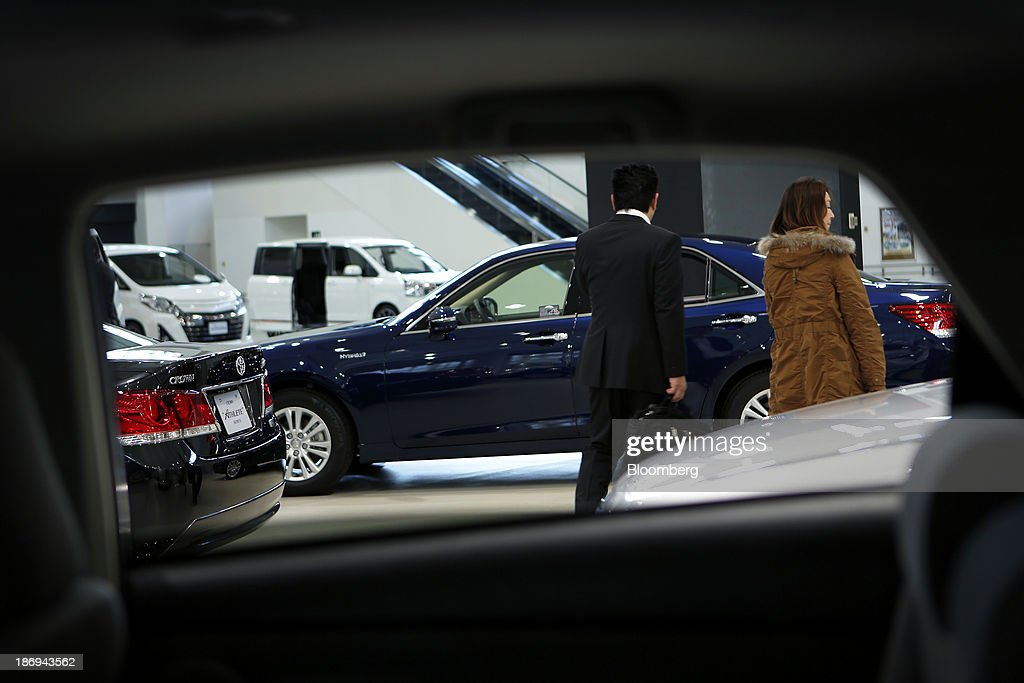 Visitors are seen through a frame of a car window as they look at a Toyota Motor Corp. Crown Royal sedan, blue in center, while a Crown Athlete sedan, left, stands on display at the company's showroom in Tokyo, Japan, on Tuesday, Nov. 5, 2013. Toyota, the world's largest automaker, will probably deliver record semiannual profit when it reports earnings tomorrow, as the weaker yen bolsters the value of Japanese cars sold overseas. Photographer: Kiyoshi Ota/Bloomberg via Getty Images