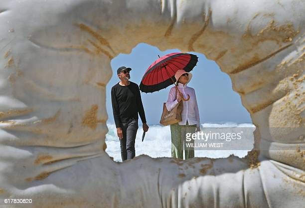 Visitors are seen through a sculpture on Tamarama Beach which was rescued from the surf as large swells damaged sculptures at the Sculpture by the...