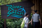 Visitors are seen walking past a sign directing them to the River Safari during a media tour ahead of the opening of River Safari at the Singapore...
