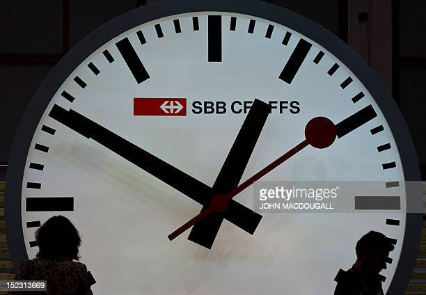 Visitors are silhouetted against a giant railway clock at the Swiss railway stand at the Innotrans 2012 International Trade Fair for Transport and...