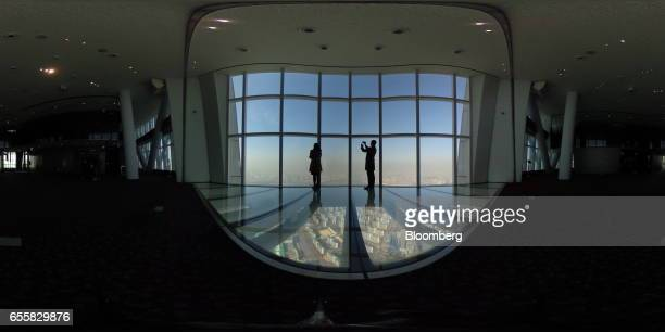 Visitors are silhouetted as they take photographs from the glassbottomed observation deck at the Lotte Corp World Tower in Seoul South Korea on...
