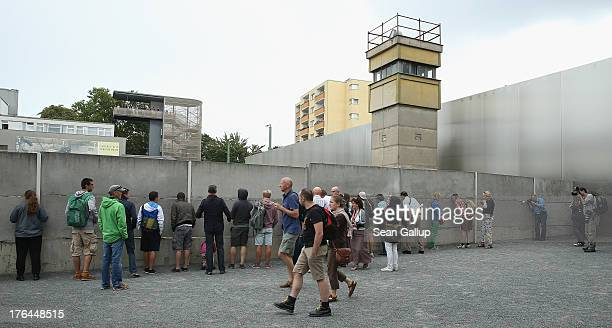 Visitors arrive at a section of the former Berlin Wall and a guard tower at the Berlin Wall memorial at Bernauer Strasse on the 52nd anniversary of...