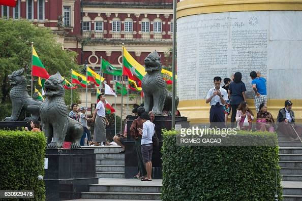 Visitors arrive at the Independence Monument in Yangon's central Mahabandoola park decorated with national flags following the dawn flagraising...