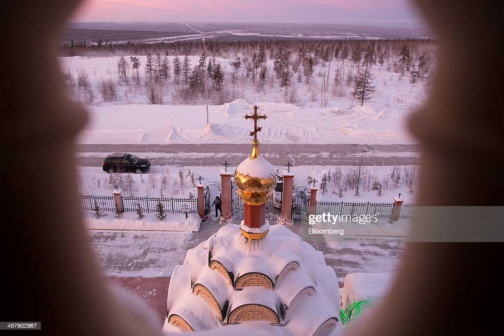 Visitors arrive for a Sunday service at the orthodox church of Saint Seraphim of Sarov seen from the bell tower in the mining town of Udachny, Sakha Republic, Russia, on Sunday, Dec. 15, 2013. Russia plans to maintain control of Mirny-based Alrosa, which produces a quarter of the world's diamonds by value and more rough diamonds than De Beers by carat. Photographer: Andrey Rudakov/Bloomberg via Getty Images