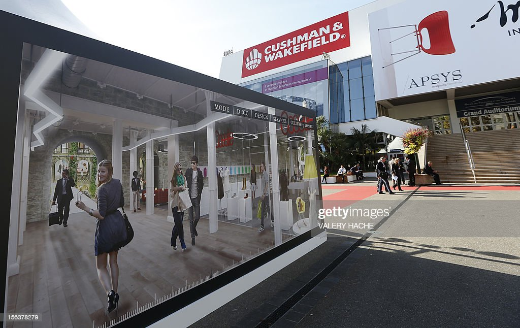 Visitors arrive for the opening of the International Market for Retail Real Estate (MAPIC) on November 14, 2012 in the southeastern French city of Cannes. The event held until November 16, gathers thousands of retailers, investors, local and regional authorities, and retail property professionnals from around the world. AFP PHOTO / VALERY HACHE