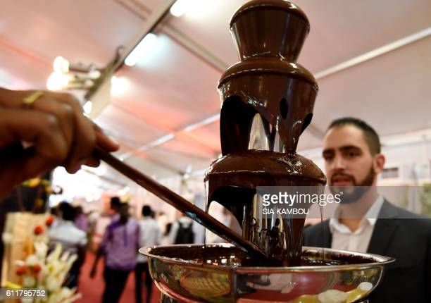 Visitors arrive to taste chocolate from a fountain a stand in Abidjan on October 1 2016 during the national days of cocoa and chocolate Ivory Coast...