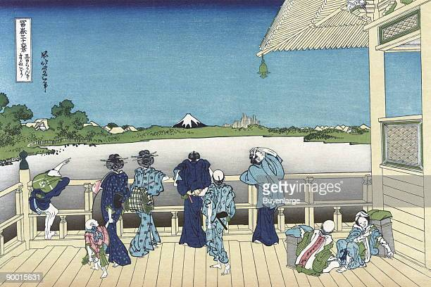 Visitors at a temple overlook a lake and into the distance Mt Fuji while children play on the deck of the porch