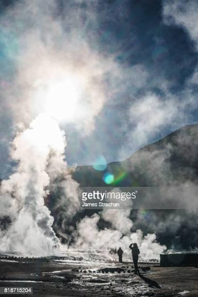 Visitors at dawn watching the sulfur-rich geysers shoot upwards at high altitude (4320m) Geisers de Tatio, near San Pedro de Atacama, Chile