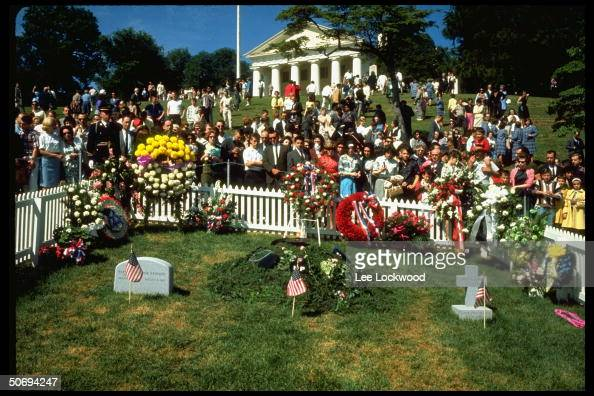 Visitors at grave site paying respects to slain President John F Kennedy on first birthday after assassination as military guard stands by