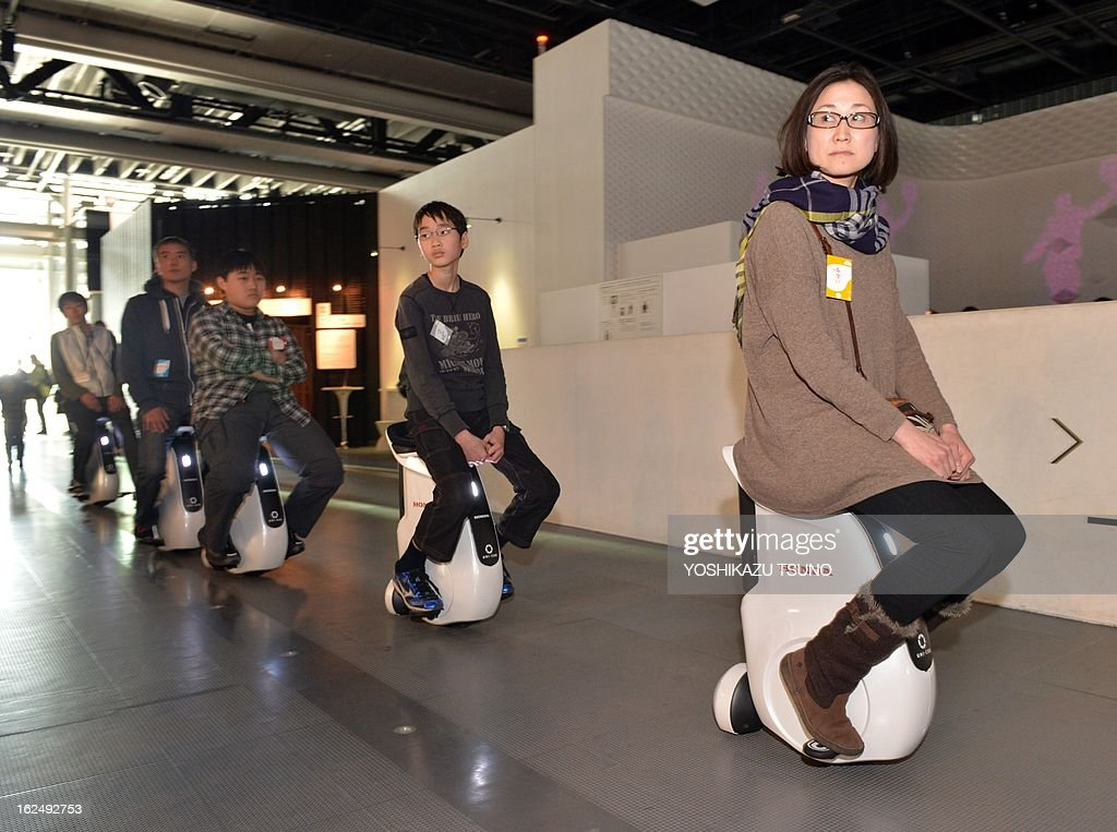Visitors at the National Museum of the Emerging Science and Innovation drive the personal mobility devices 'UniCub' by Japanese automaker Honda in...