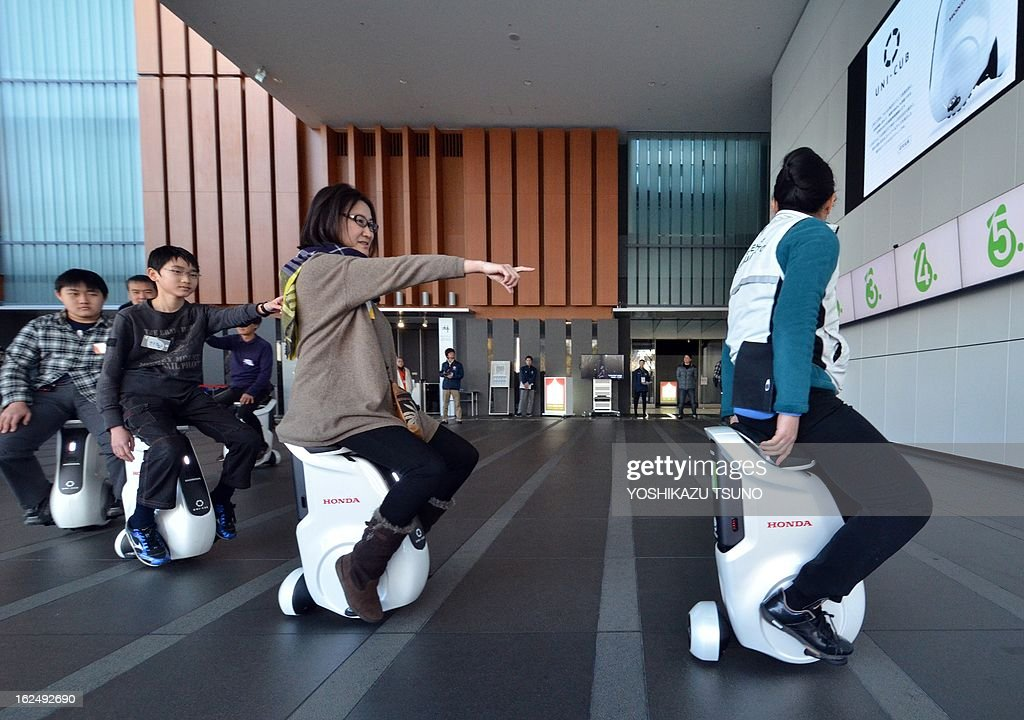 Visitors at the National Museum of the Emerging Science and Innovation learn to drive the personal mobility devices 'Uni-Cub' by Japanese automaker Honda, in Tokyo on February 24, 2013. The science museum started curator's guide tours for visitors using the saddle style mobility. AFP PHOTO / Yoshikazu TSUNO