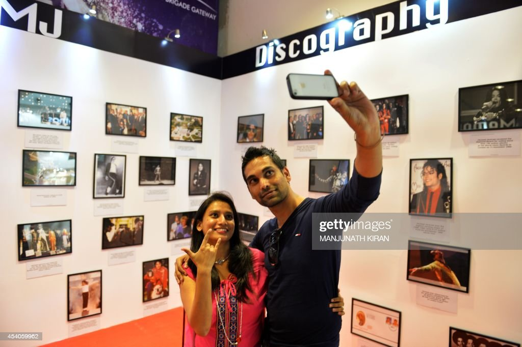 Visitors at the Orion Mall take a a selfie at a photo gallery of late US pop star Michael Jackson, set up at the mall as part of birthday celebrations for the late music icon, in Bangalore on August 23, 2014. Fans of the lengendary pop star Michael Jackson, who passed away in 2009, are gearing up to celebrate what would have been his 56th birthday on August 29. AFP PHOTO/Manjunath KIRAN