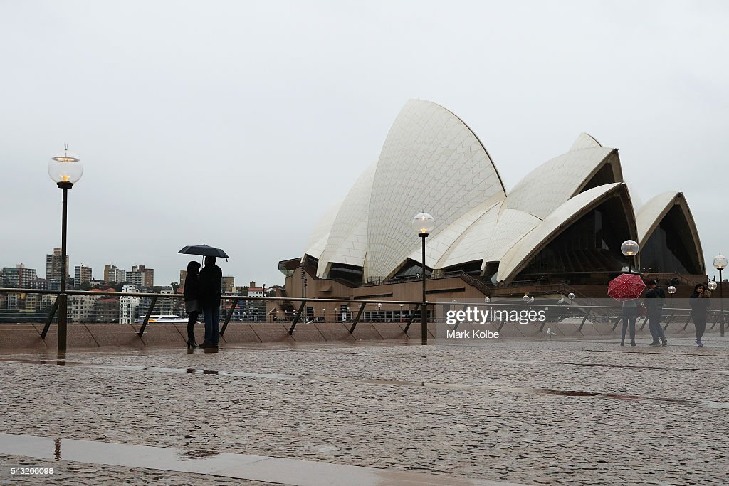Visitors at the Sydney Opera House huddle under an umbrella on June 27, 2016 in Sydney, Australia. Sydney experienced its coldest day of the year on Sunday, and more icy weather is forecast for later in the week when a second cold front hits later in the week.
