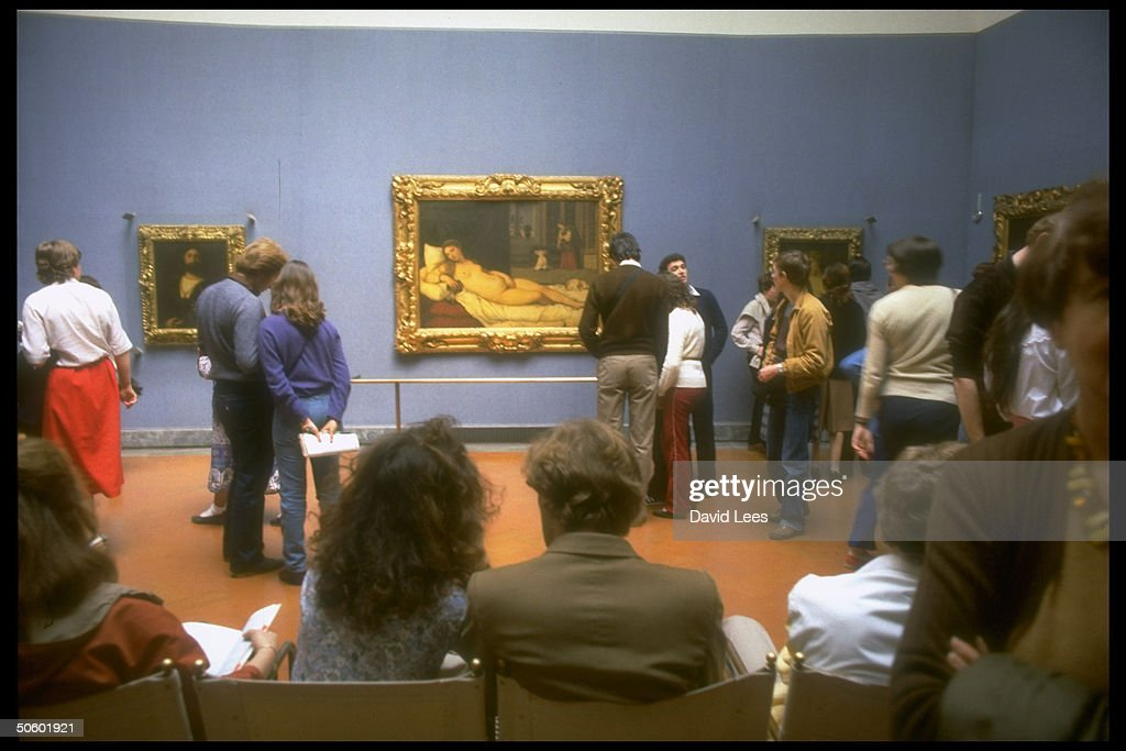 Visitors at the Uffizi Museum milling around gallery, with Titian's Venus of Urbino (ca. 1538) clearly visible in bkgrd.