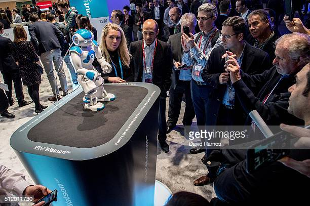Visitors attend a demonstration of a robot named 'Watson' at the IBM stand on day 3 of the Mobile World Congress 2016 on February 24 2016 in...