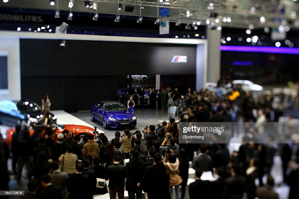 Visitors attend a news conference hosted by Bayerische Motoren Werke AG (BMW) in this photograph taken with tilt-shift lens during the press day of the Seoul Motor Show in Goyang, South Korea, on Thursday, March 28, 2013. The show runs from today until April 7. Photographer: SeongJoon Cho/Bloomberg via Getty Images